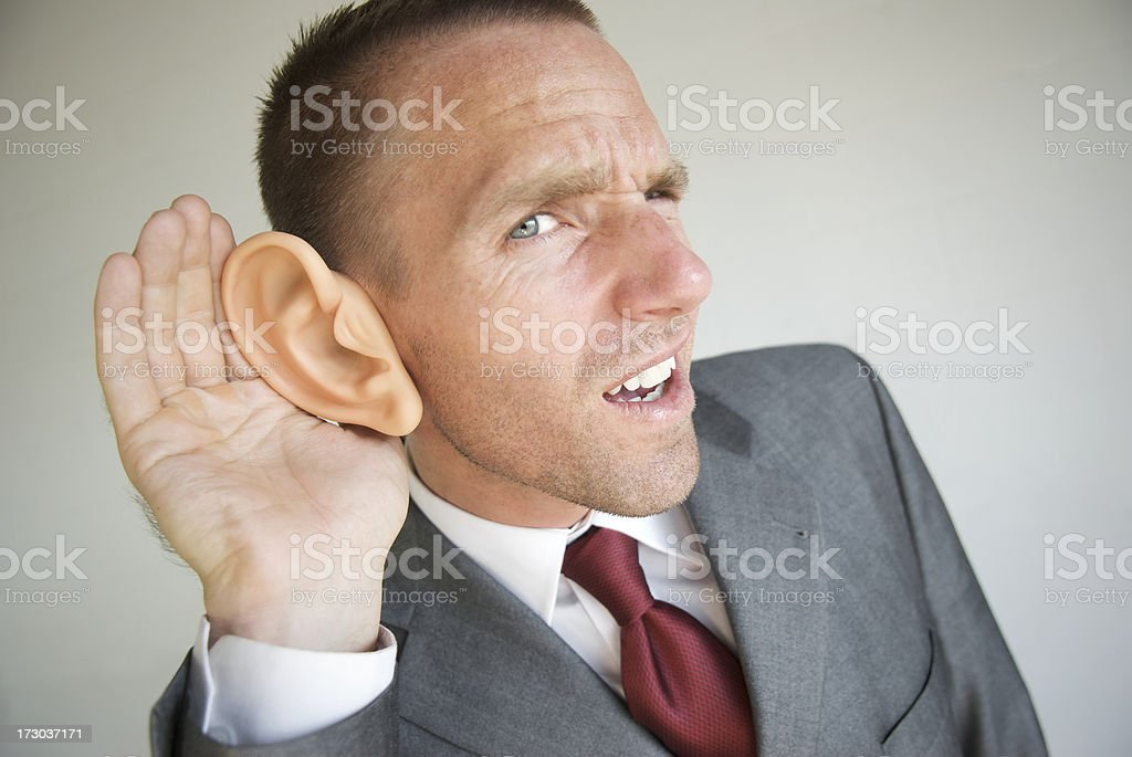 Businessman Cups a Big Ear and Strains to Listen stock photo