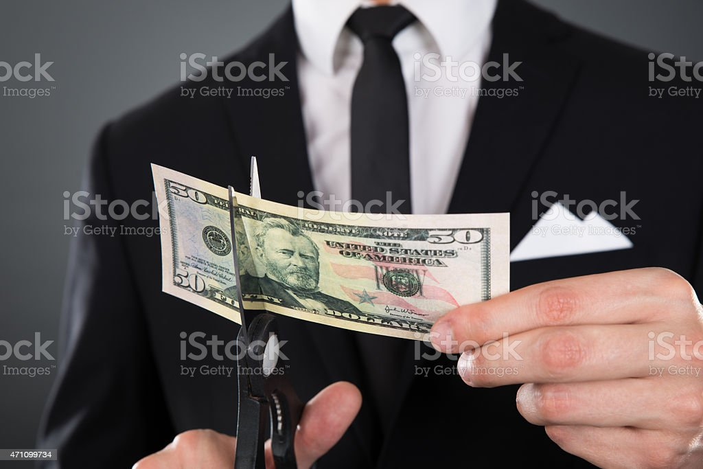 Businessman Cutting Dollar Bill With Scissors stock photo