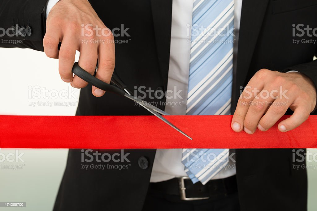 Businessman Cutting Red Ribbon With Scissors stock photo