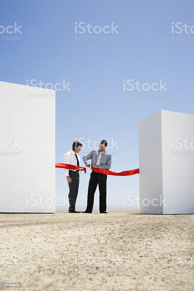 Businessman cutting red tape or ribbon between two walls royalty-free stock photo