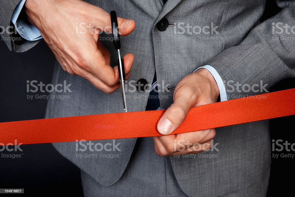 Businessman cutting ribbon stock photo