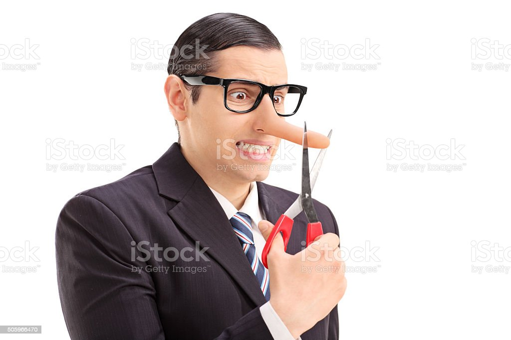Businessman cutting the tip of his long nose stock photo