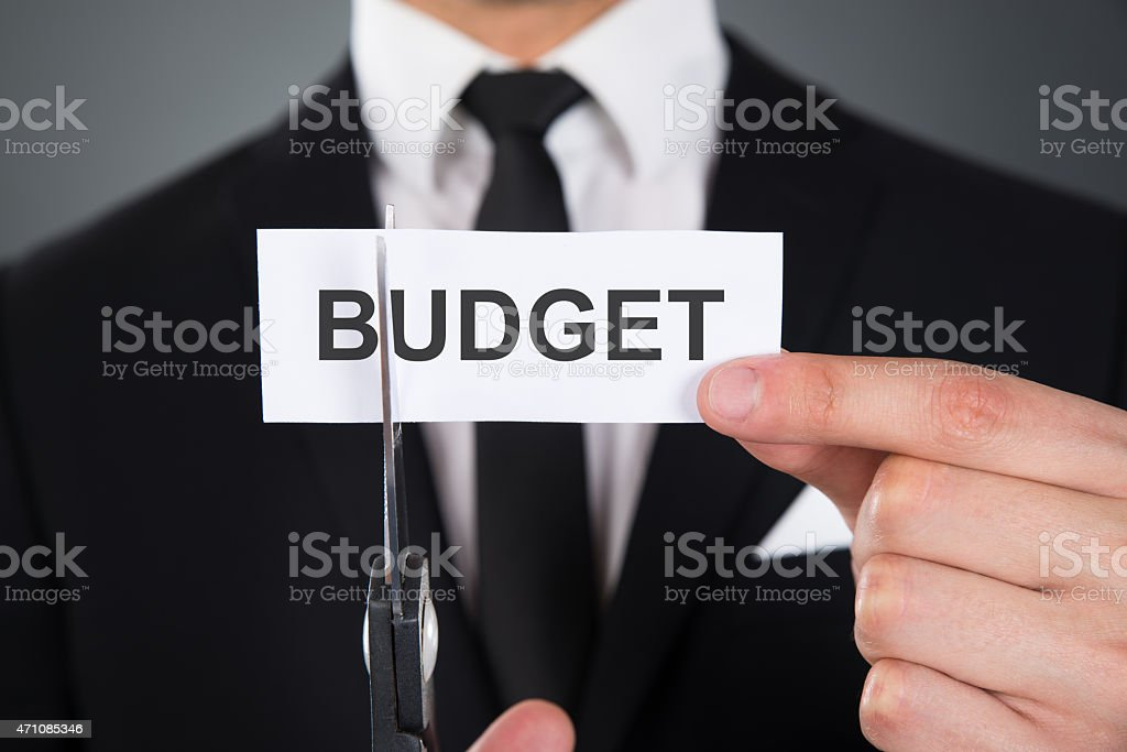 Businessman Cutting The Word Budget On Paper With Scissors stock photo