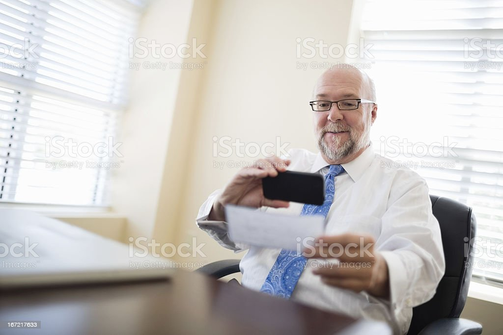 Businessman depositing check via smartphone from his office stock photo
