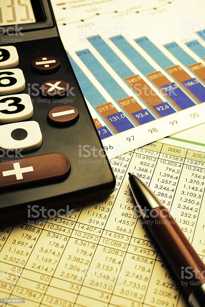 Businessman desk - calculator, financial figures and pen royalty-free stock photo