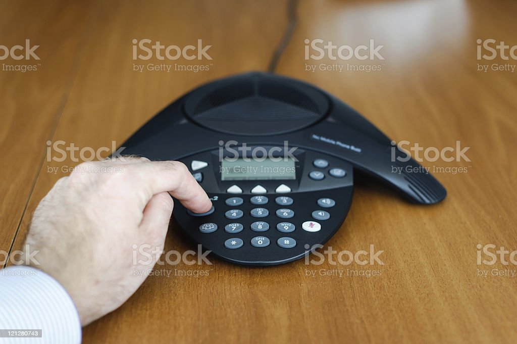 Businessman dialing conference call stock photo