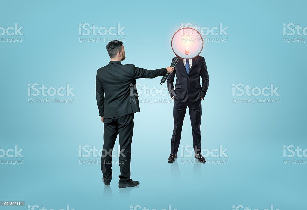 Businessman directing magnifying glass on lamp-headed man stock photo