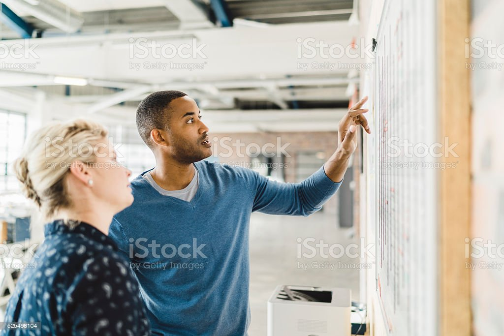 Businessman discussing with colleague over whiteboard stock photo