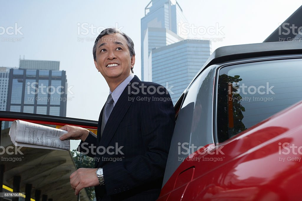 Businessman Disembarking From Cab stock photo