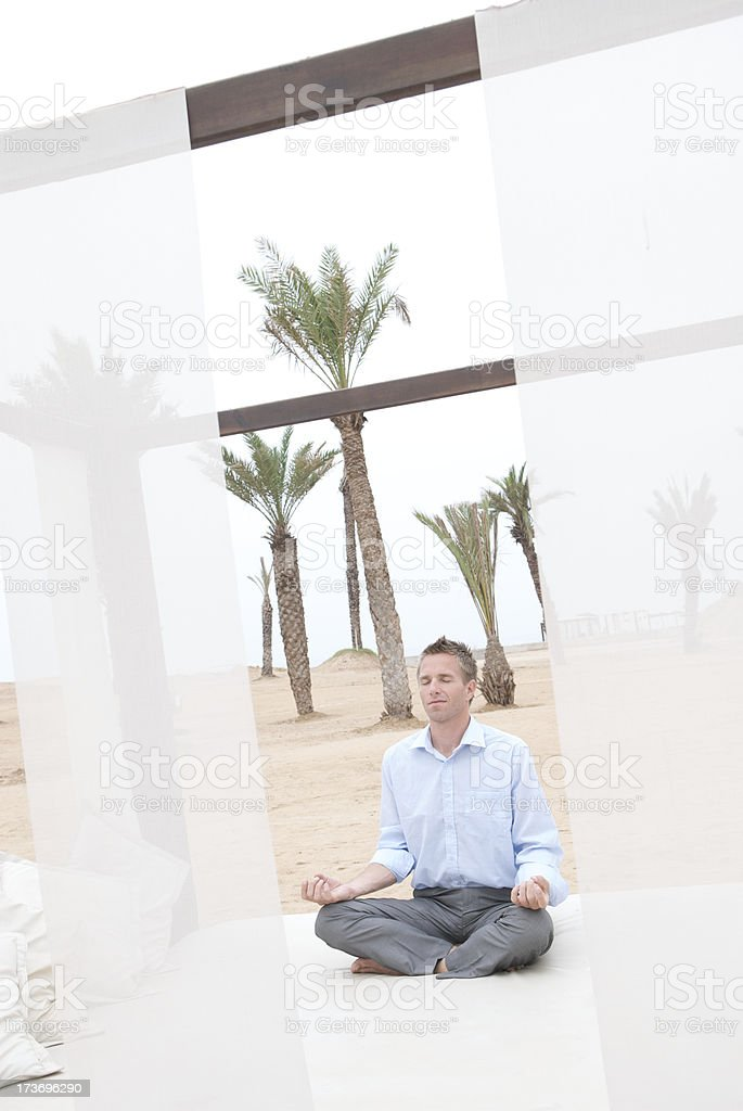 Businessman Does Yoga in Desert Oasis stock photo