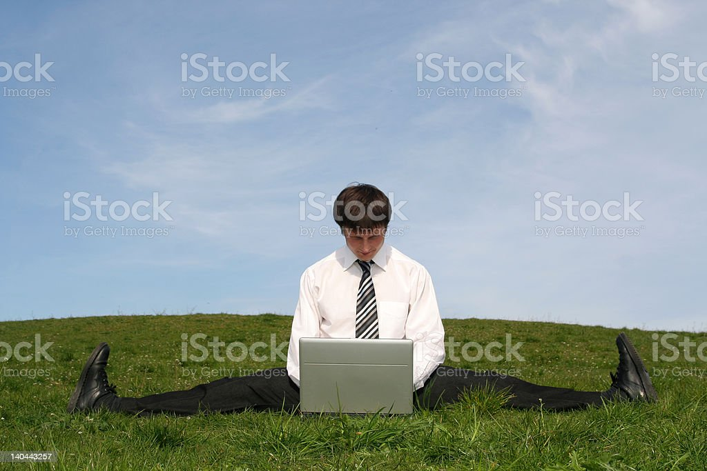 Businessman doing a split and using laptop stock photo