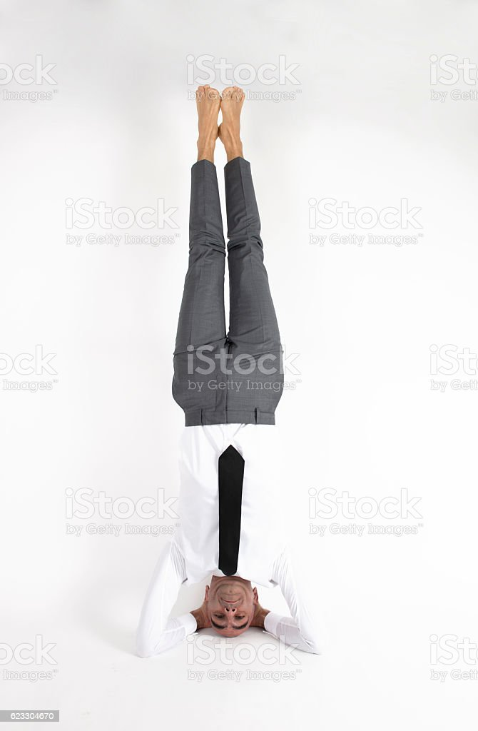 Businessman Doing Headstand On White Background stock photo