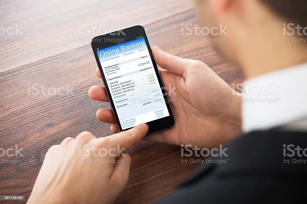 Businessman Doing Online Banking On Mobile Phone stock photo