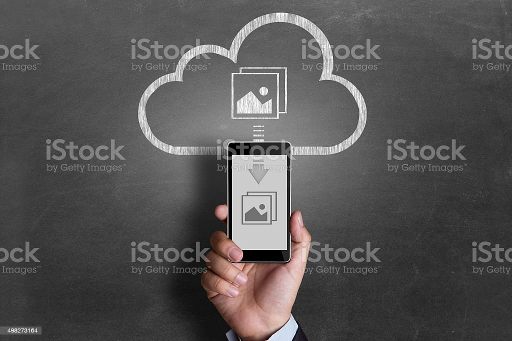 Businessman downloading pictures from cloud storage stock photo