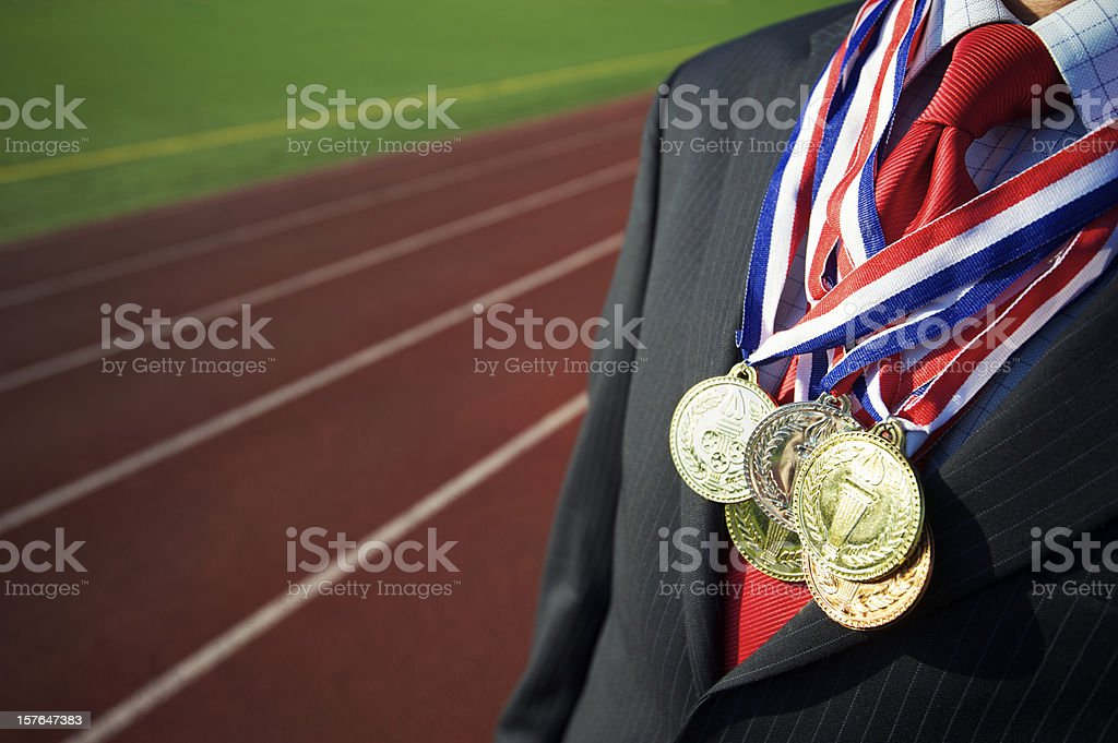 Businessman Draped with Medals Running Track Background stock photo