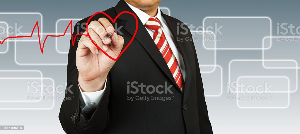 Businessman draw a pulse line with heart stock photo