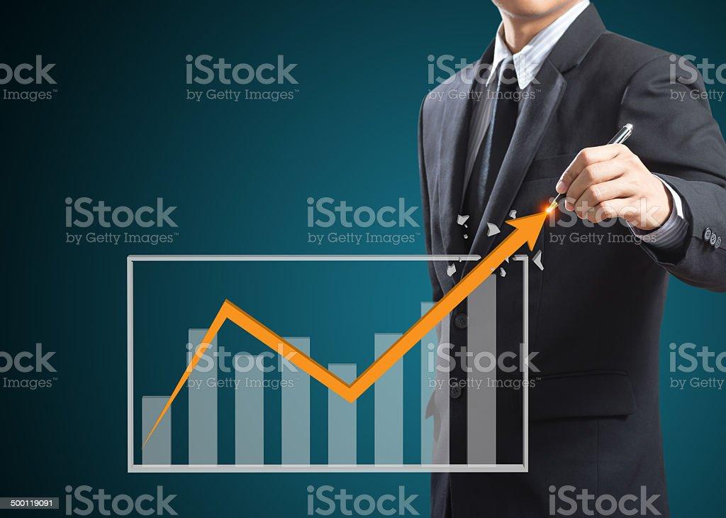 Businessman drawing a growth arrow stock photo