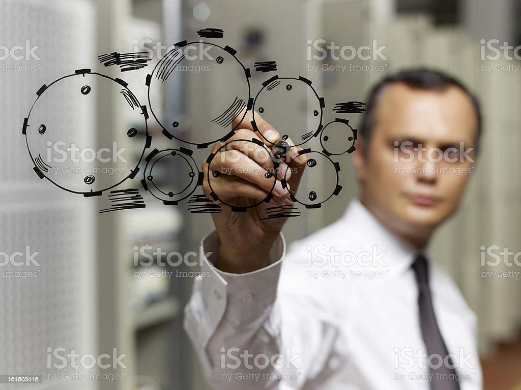 Businessman drawing gear wheel. stock photo