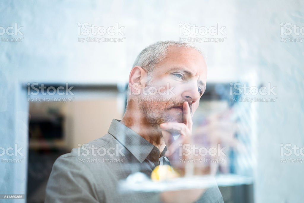 Businessman drawing graph on glass wall stock photo