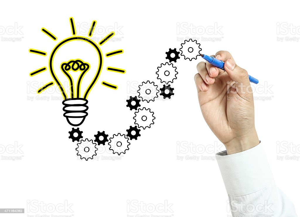 Businessman drawing light bulb and gears stock photo
