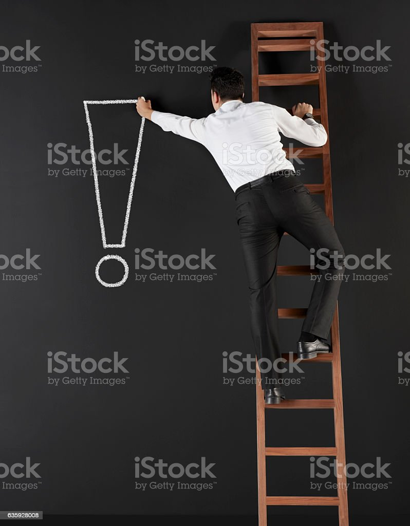 Businessman drawing punctuation mark all over black board stock photo