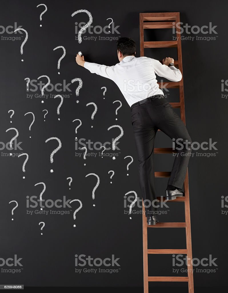 Businessman drawing question marks all over black board stock photo