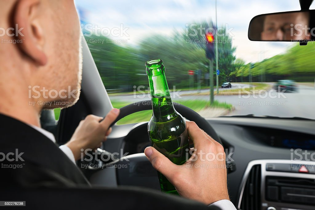Businessman Drinking Beer While Driving Car stock photo