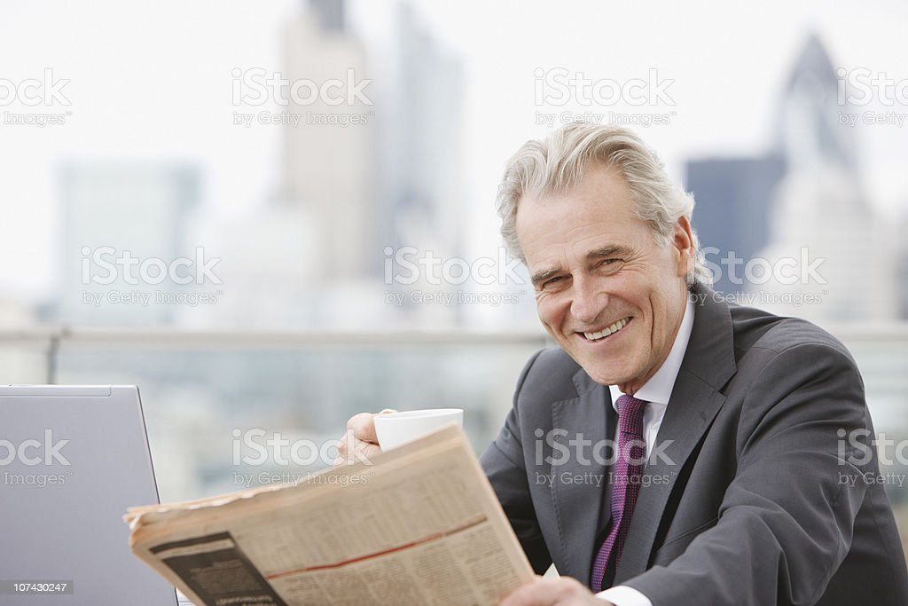 Businessman drinking coffee and reading newspaper royalty-free stock photo