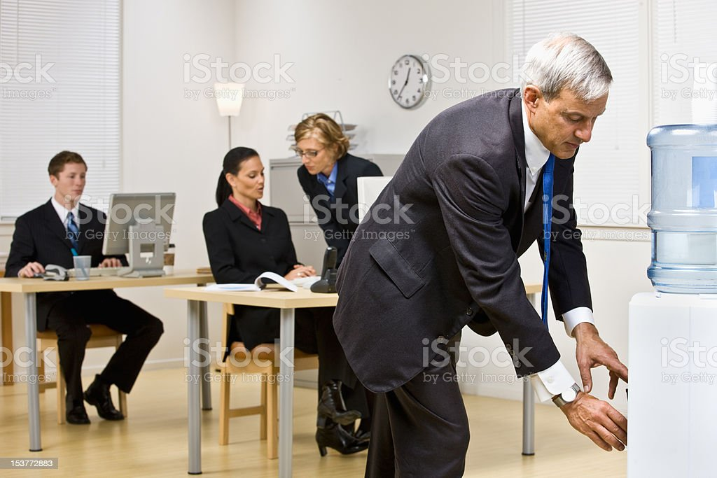 Businessman Drinking from Water Cooler stock photo