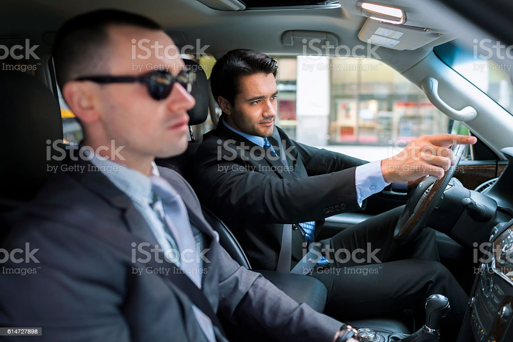 Businessman driver pointing something to his partner stock photo