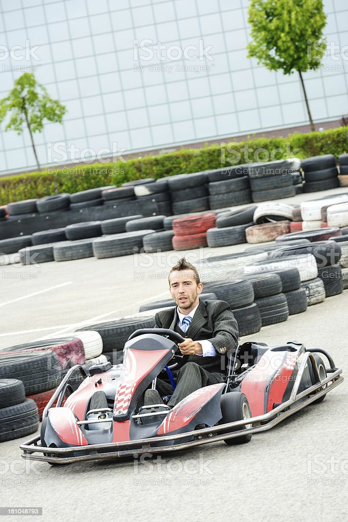 Businessman driving a go kart royalty-free stock photo
