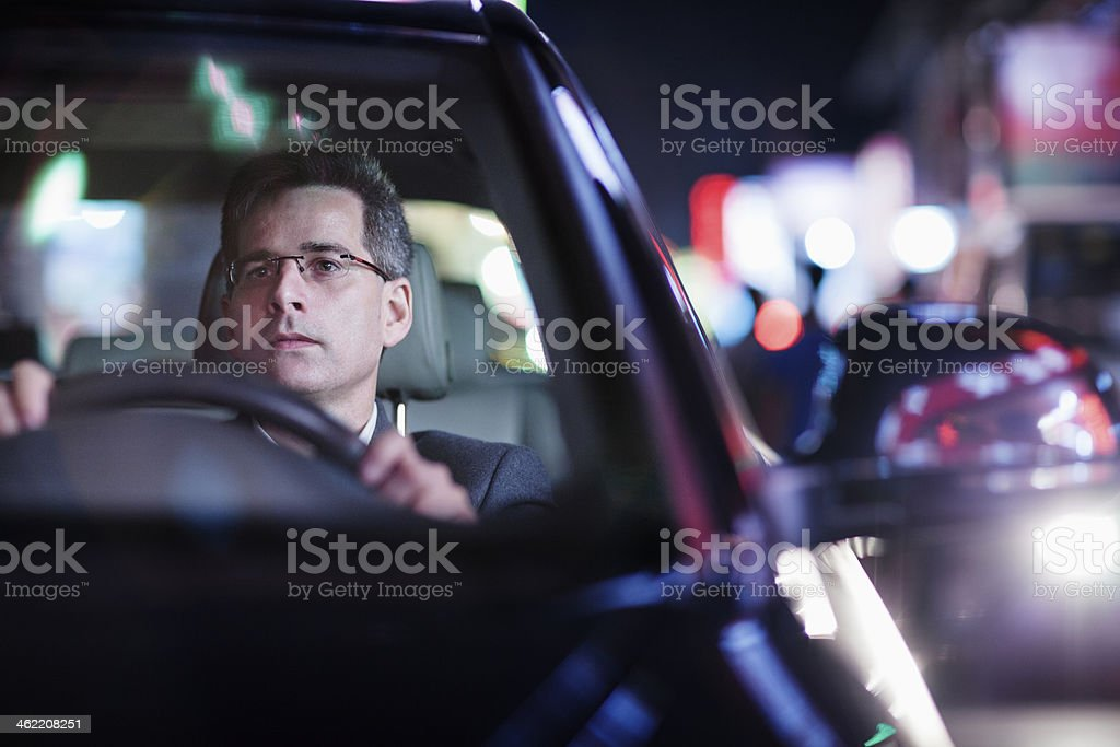 Businessman driving at night in the city stock photo