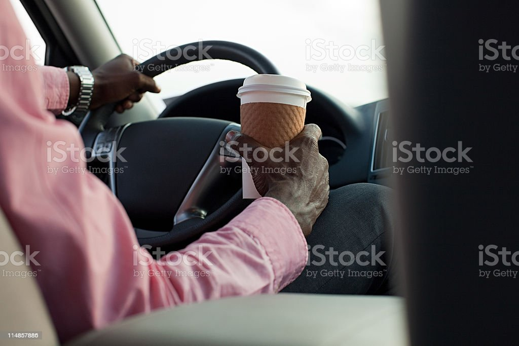 Businessman driving car with disposable cup stock photo