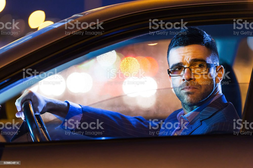 Businessman driving his car by night stock photo