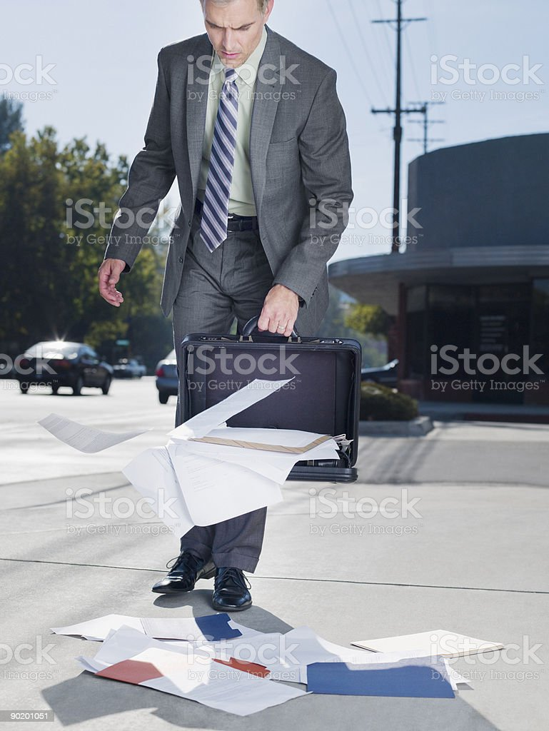 Businessman dropping papers from briefcase royalty-free stock photo