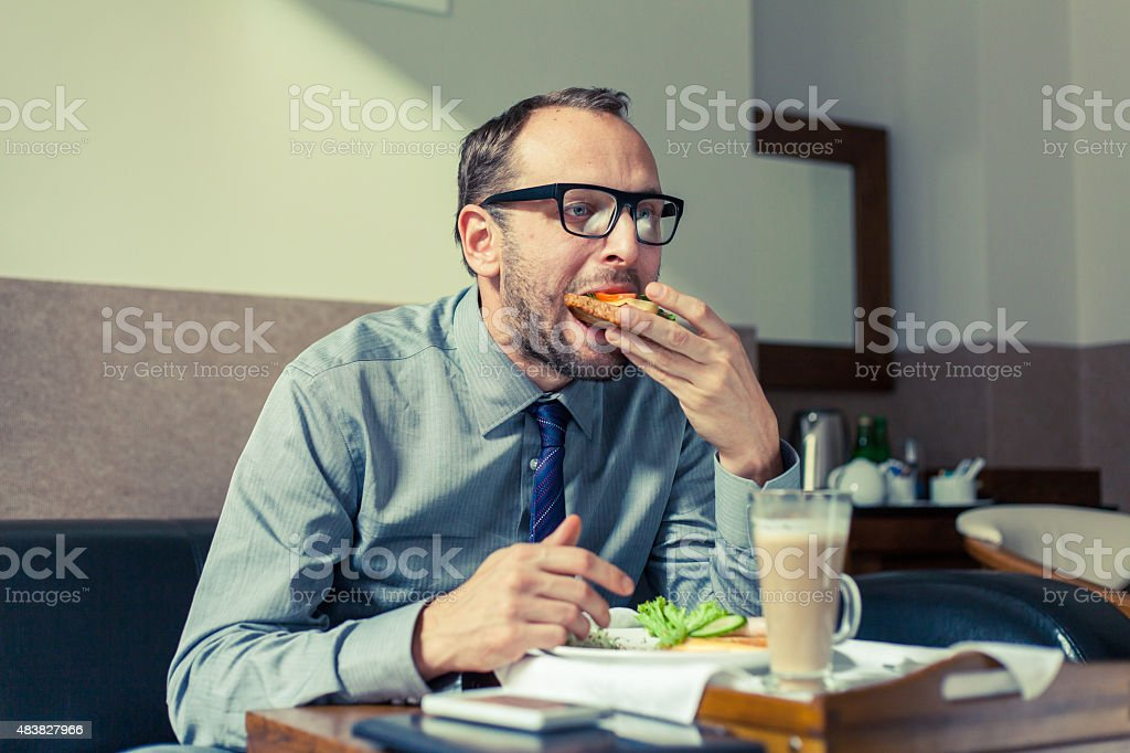 Businessman eating breakfast at home/hotel. Indoor photo. stock photo