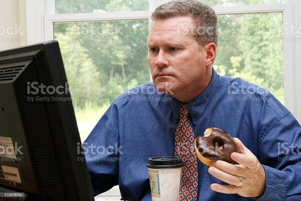 Businessman eating doughnut and coffee at computer royalty-free stock photo