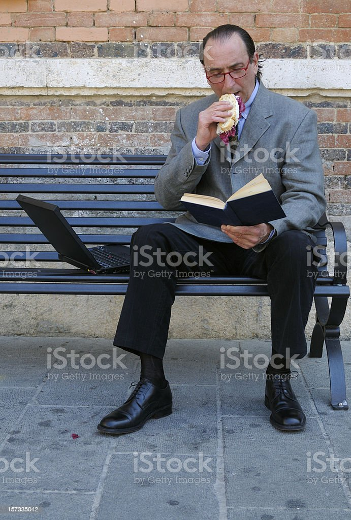 Businessman Eating Snack Reading Book on a Bench royalty-free stock photo