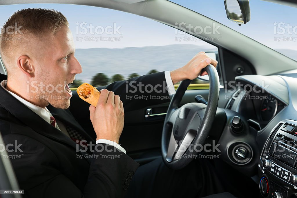 Businessman Eating Snack While Driving stock photo