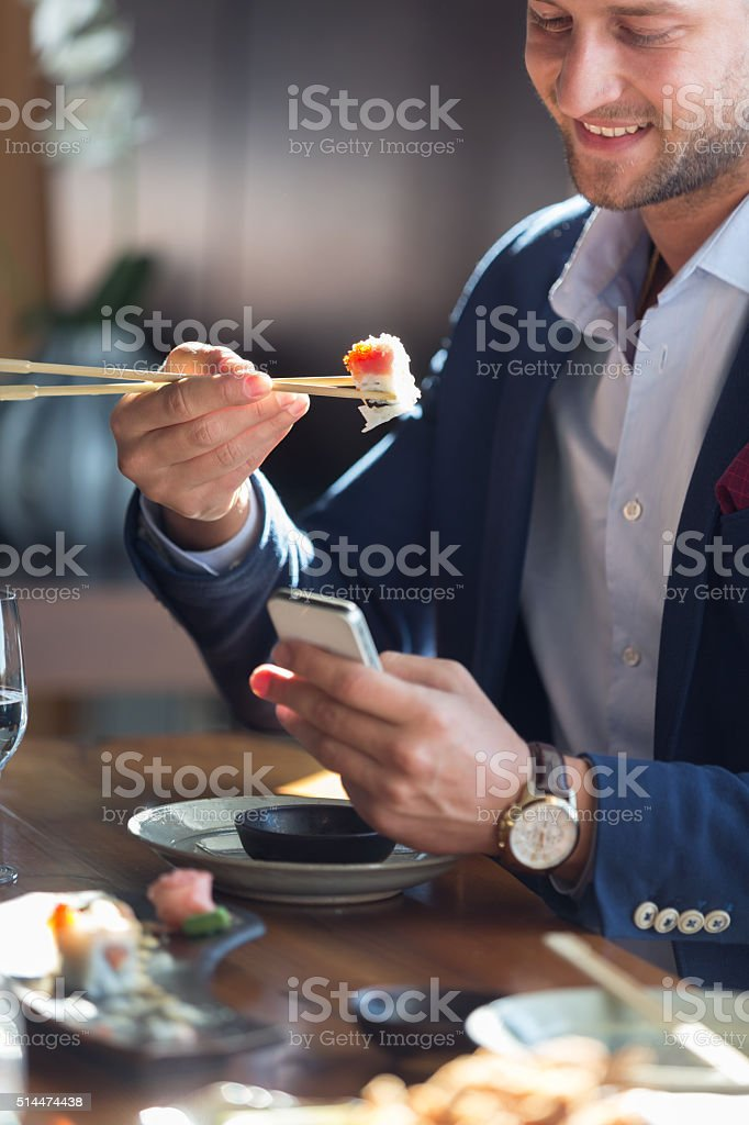 Businessman eating sushi and text messaging stock photo