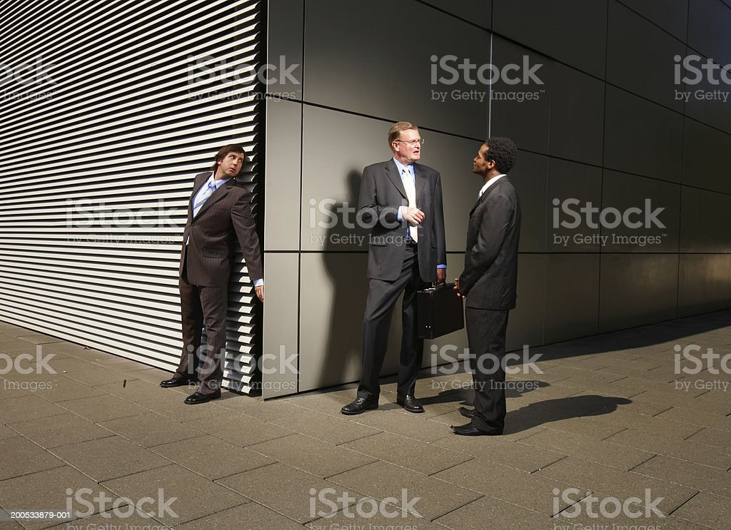 Businessman eavesdropping on conversation at street corner stock photo