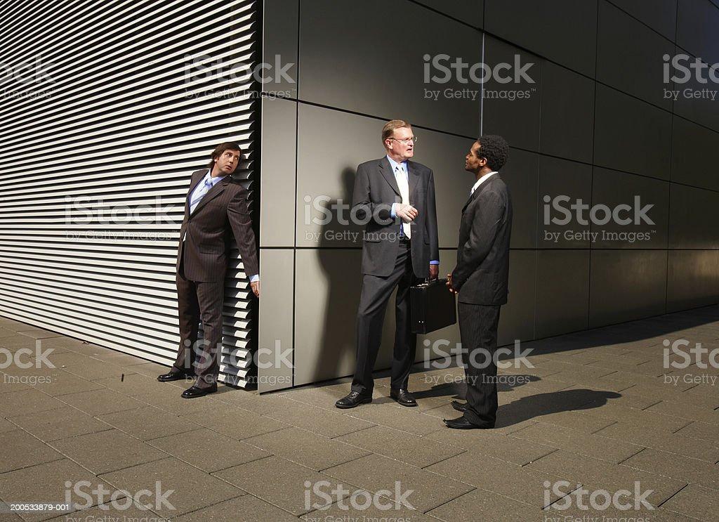 Businessman eavesdropping on conversation at street corner stock photo