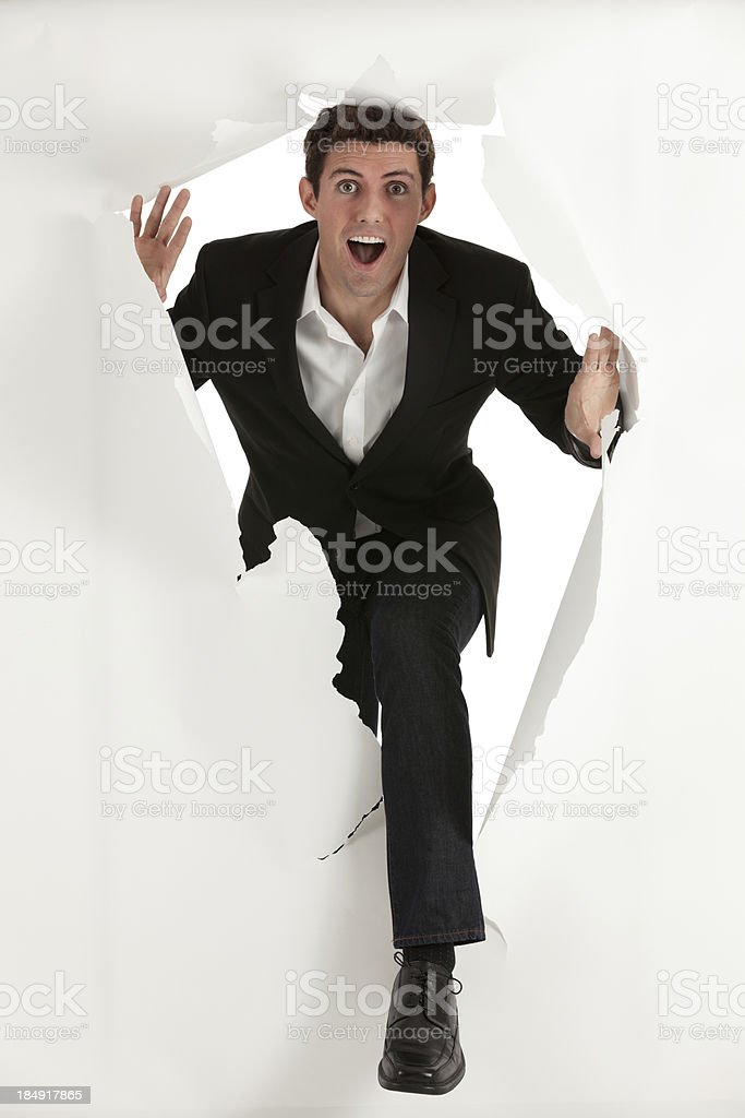 Businessman emerging from a hole of paper stock photo