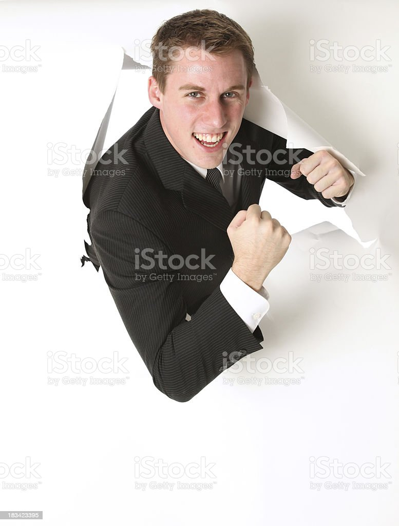 Businessman emerging through a hole in white paper royalty-free stock photo