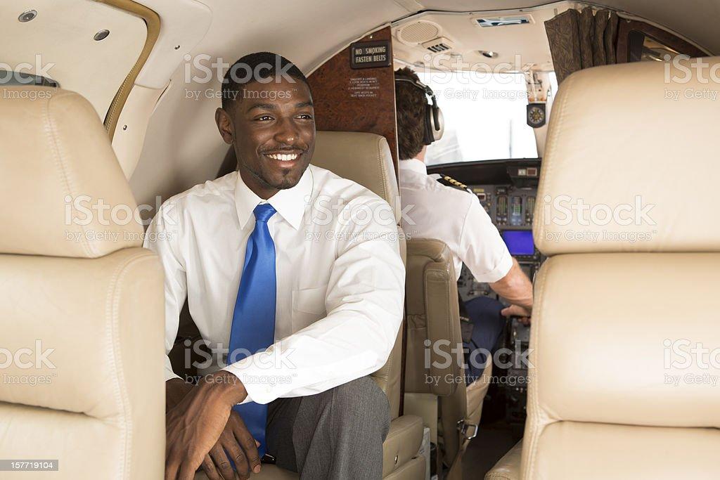 Businessman enjoying his business class flight on private jet stock photo