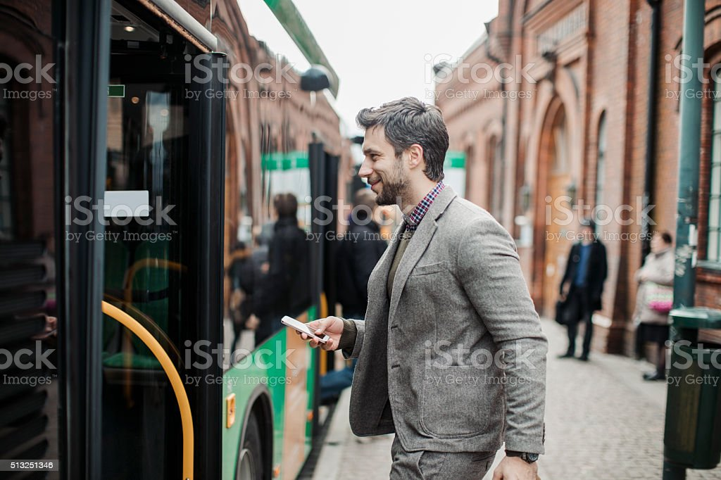 Businessman entering a bus stock photo