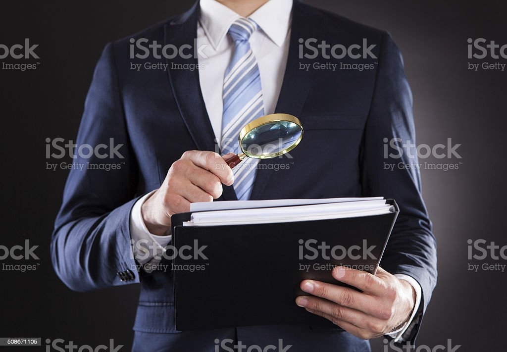 Businessman Examining Documents With Magnifying Glass stock photo