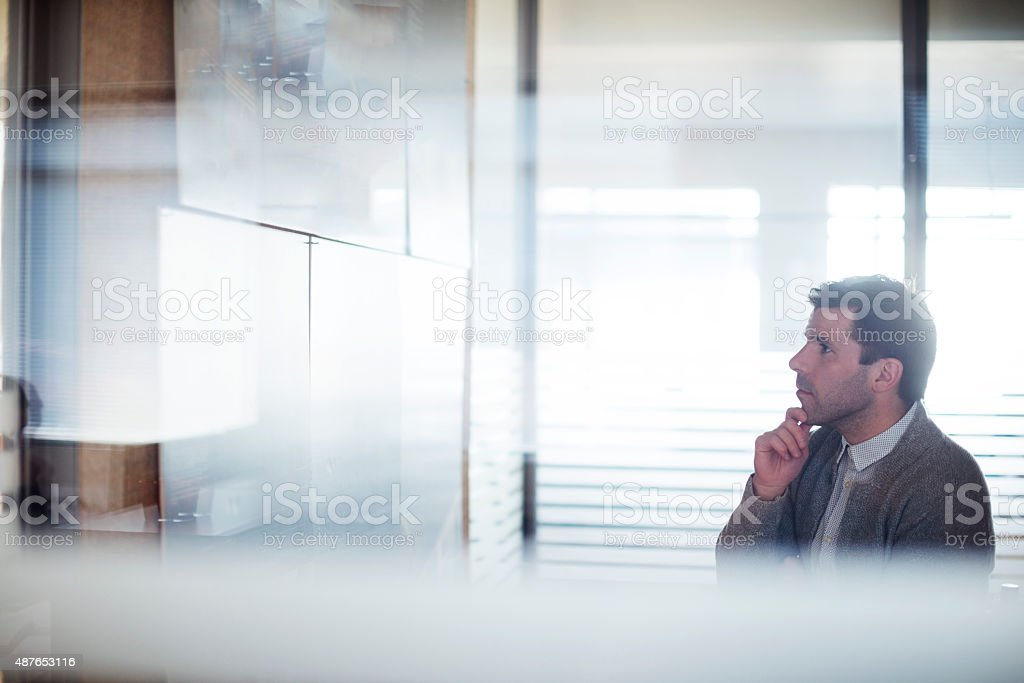 Businessman examining plan on wall in brightly lit office stock photo