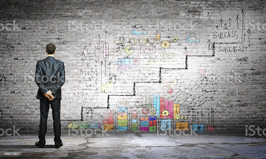 Businessman examining wall with success graffiti stock photo