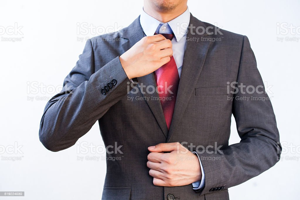Businessman Executive adjusting red tie isolated on white background stock photo